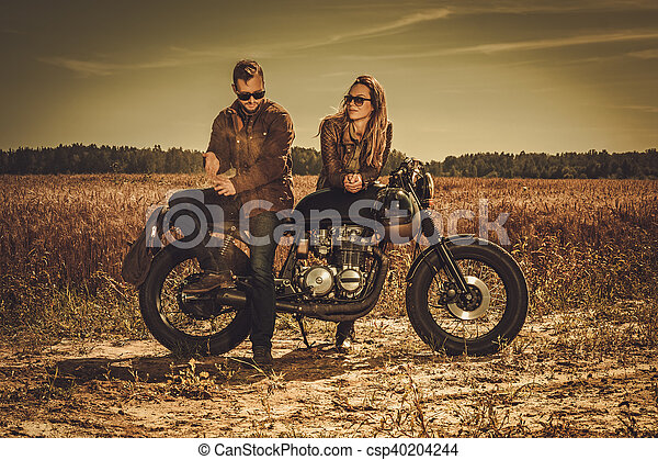 Stylish cafe racer couple on the vintage custom motorcycles in a field. - csp40204244