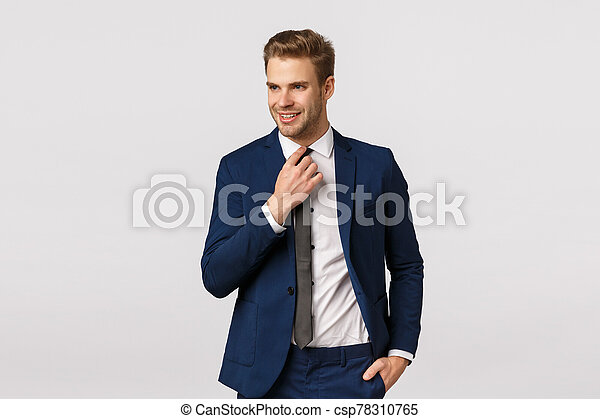 Stylish, confident and assertive blond handsome male entrepreneur in classic suit, getting ready for corporate dinner, business meeting, adjusting tie and looking away with lucky, determined smile - csp78310765