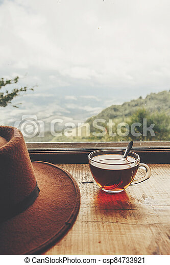 stylish hipster hat and glass of hot tea on wooden table at window light with view on mountains and sky. delicious drink on mountain top. summer travel and wanderlust. space for text - csp84733921