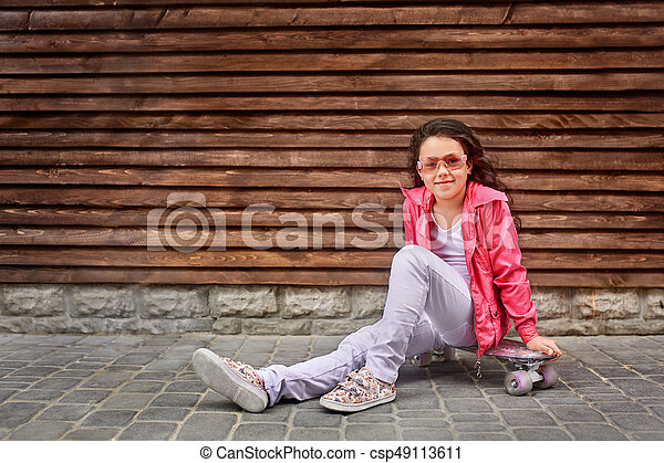 Stylish little girl child wearing a summer or autumn pink jacket, white jeans, sunglasses - csp49113611