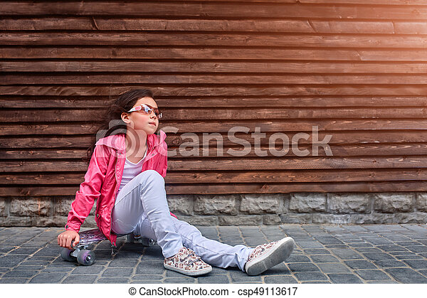 Stylish little girl child wearing a summer or autumn pink jacket, white jeans, sunglasses - csp49113617
