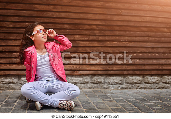 Stylish little girl child wearing a summer or autumn pink jacket, white jeans, sunglasses - csp49113551