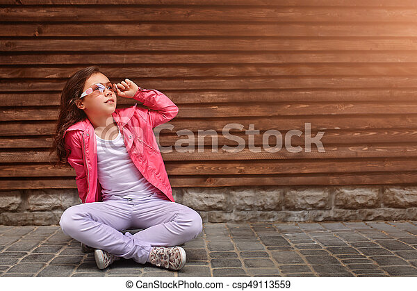 Stylish little girl child wearing a summer or autumn pink jacket, white jeans, sunglasses - csp49113559