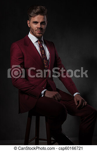 Stylish Man In Grena Suit Sitting On A Wooden Chair
