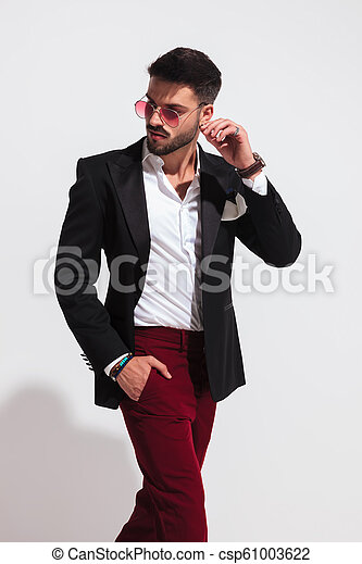 5eb13f4423 Stylish young man stepping to side and looking behind. Portrait of ...