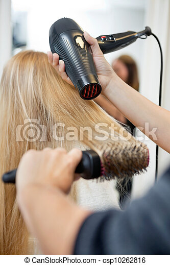 Stylist Drying Woman's Hair In Hairdresser Salon - csp10262816