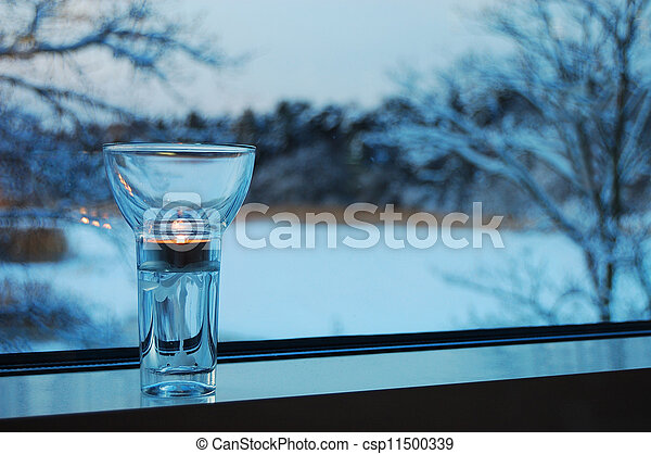 Subtle candle on a window-sill with winter forest at the background  - csp11500339