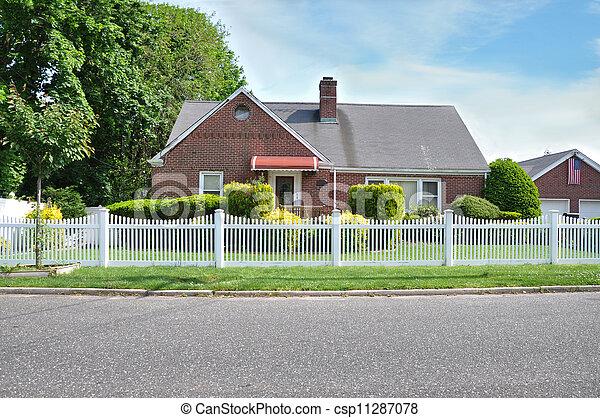 Suburban Brick Home white picket fence American Flag - csp11287078