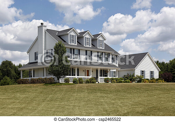 Suburban home with blue shutters and wraparound porch - csp2465522