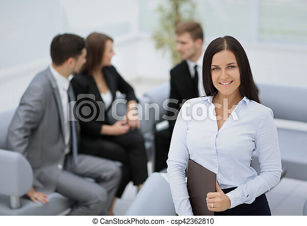 Successful business woman standing with her staff in background - csp42362810