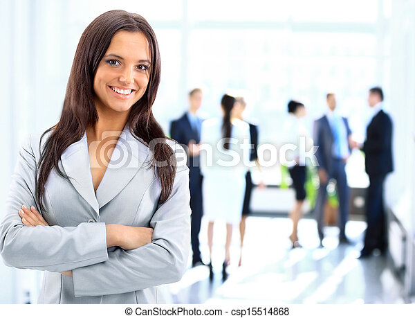 Successful business woman standing with her staff in background at office - csp15514868