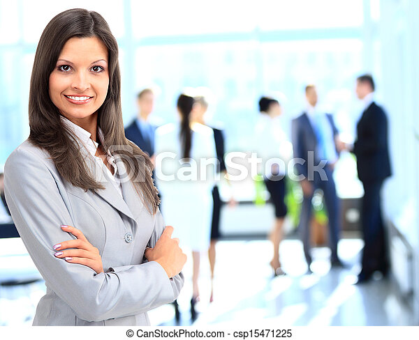 Successful business woman standing with her staff in background at office - csp15471225