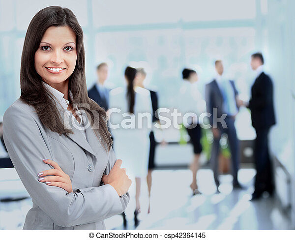 Successful business woman standing with her staff in background at office - csp42364145