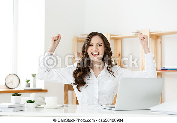 Successful business woman with arms up sitting in modern office. - csp58400984