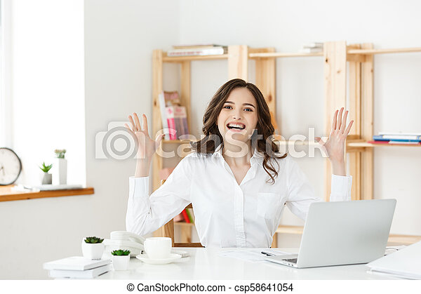 Successful business woman with arms up sitting in modern office. - csp58641054