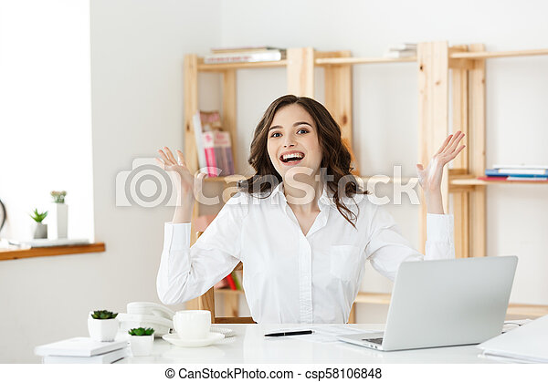 Successful business woman with arms up sitting in modern office. - csp58106848
