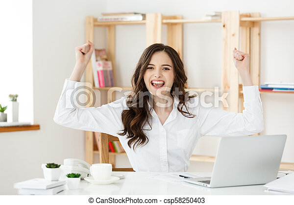 Successful business woman with arms up sitting in modern office. - csp58250403