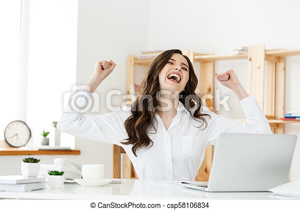 Successful business woman with arms up sitting in modern office. - csp58106834