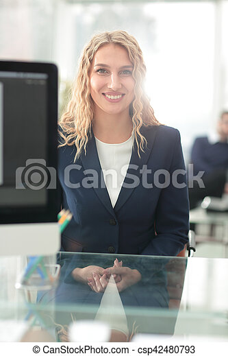 Successful business woman with her staff in background at office - csp42480793
