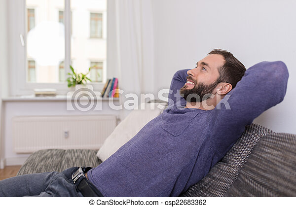 Successful man relaxing on the sofa at home - csp22683362