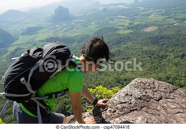 successful woman hiker climbing rock on mountain peak cliff - csp47094418