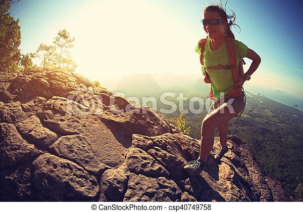 successful woman hiker climbing rock on mountain peak cliff - csp40749758