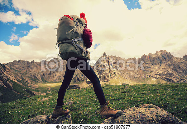 successful woman with backpack hiking in mountains - csp51907977