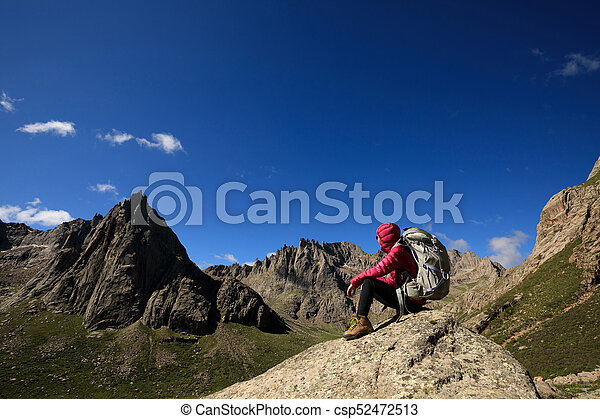 successful woman with backpack hiking in mountains - csp52472513