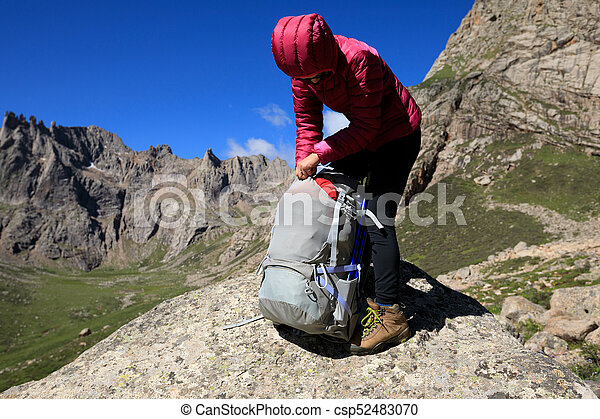 successful woman with backpack hiking in mountains - csp52483070