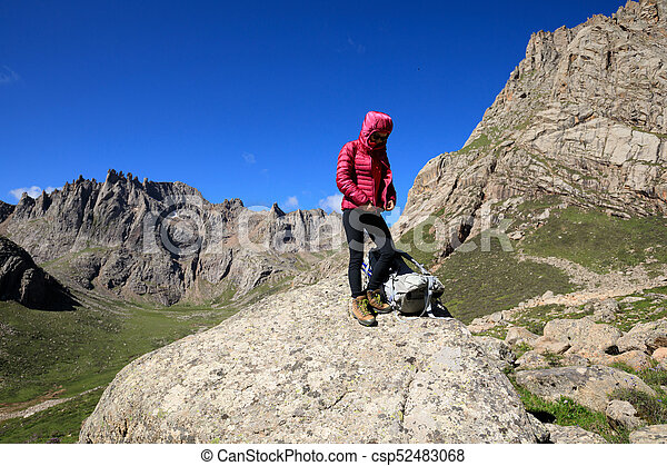 successful woman with backpack hiking in mountains - csp52483068