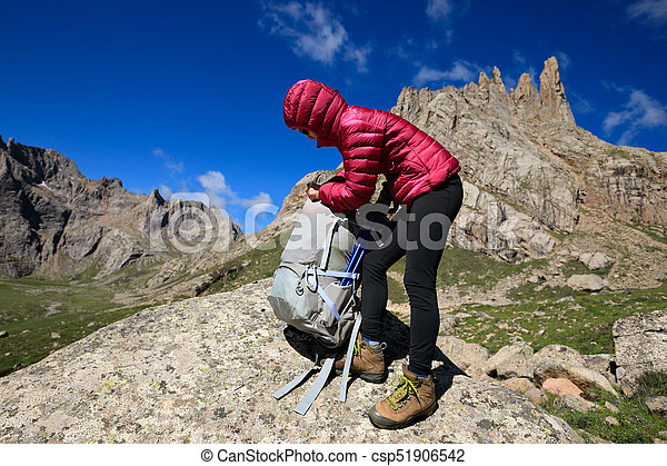 successful woman with backpack hiking in mountains - csp51906542