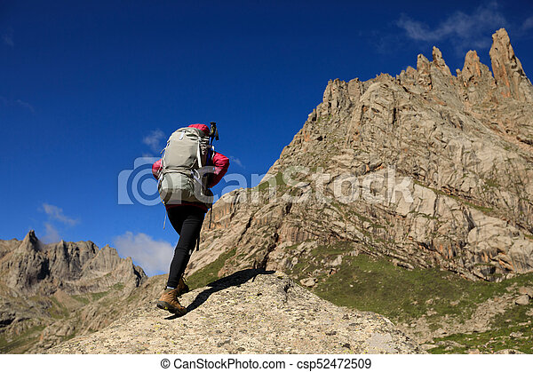 successful woman with backpack hiking in mountains - csp52472509