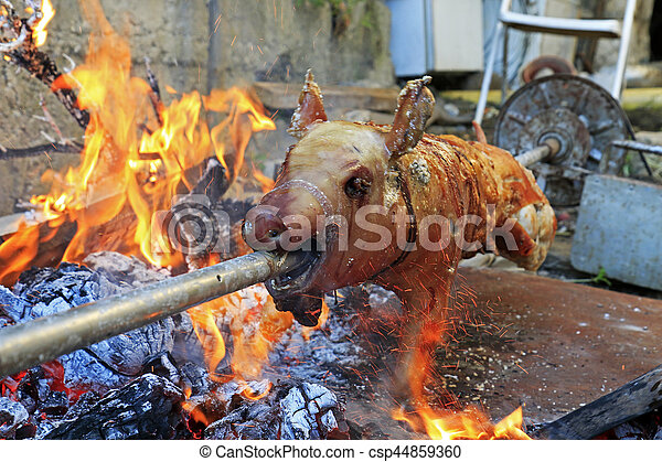 Suckling pig on a rotating spit - csp44859360