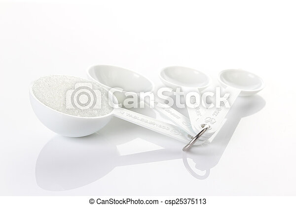 Sugar in measuring spoons on white background - csp25375113