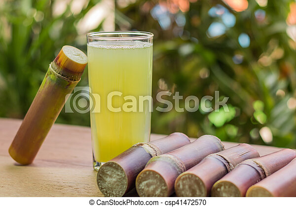Sugarcane juice with piece of sugarcane on wooden background - csp41472570