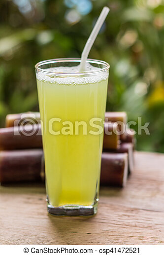 Sugarcane juice with piece of sugarcane on wooden background - csp41472521