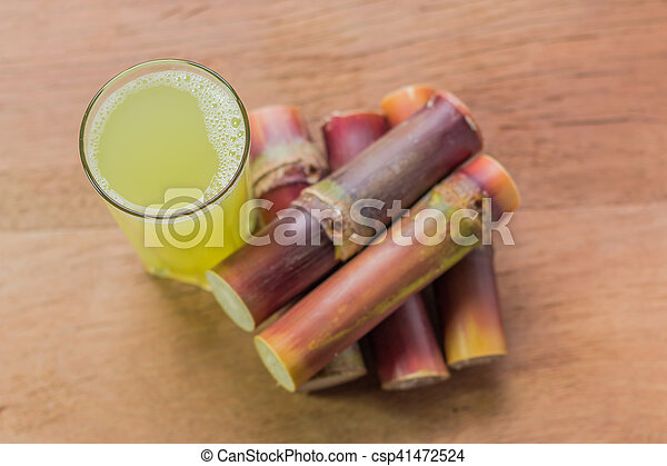 Sugarcane juice with piece of sugarcane on wooden background. Top view. - csp41472524