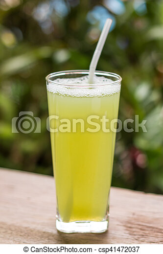 Sugarcane juice with piece of sugarcane on wooden background - csp41472037