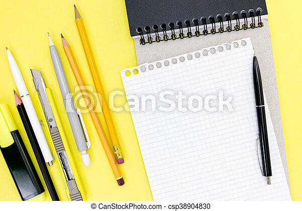 Suministros de oficina, libreta y un trozo de papel en el fondo de escritorio amarillo - csp38904830