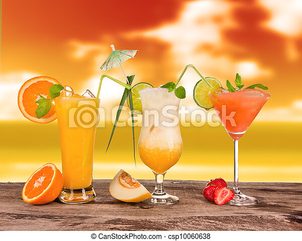 Summer cocktails in sunset with blur beach on background - csp10060638