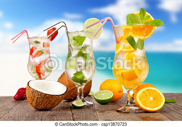 Summer cocktails with pieces of fruit on wooden table. Blur beach on background - csp13870723