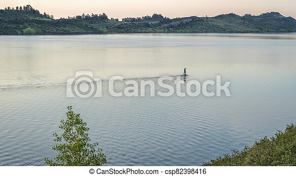 summer dawn over mountain lake with a lonely paddler - csp82398416