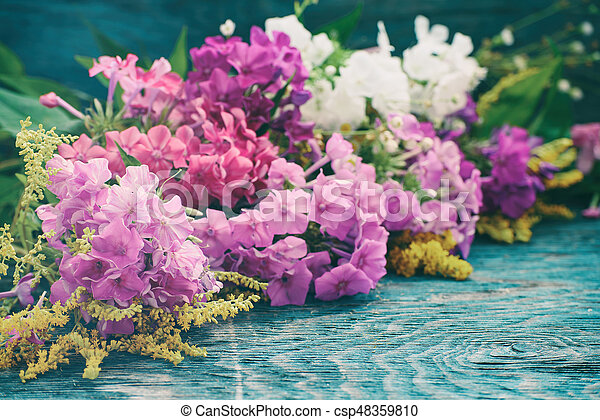 Bouquet of fresh summer flowers on the blue wooden grunge desk. Background for greeting cards, holiday postcards, invintation in vintage hipster eco rustic style with copy space