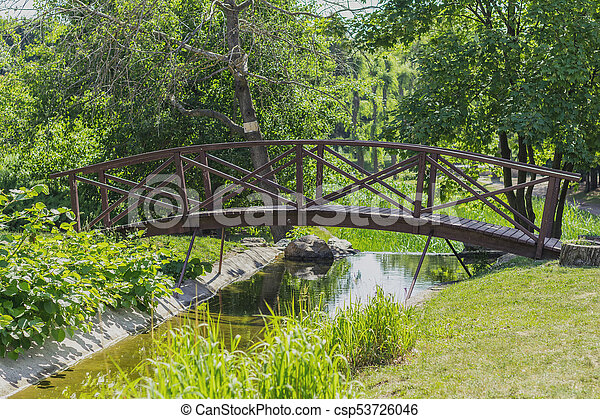 Summer footpath in the city park with a bridge on a sunny day - csp53726046