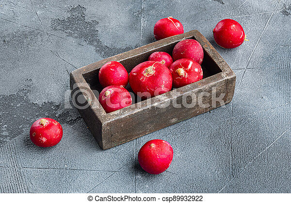Summer harvested red radish. Growing organic vegetables, in wooden box, on gray background - csp89932922