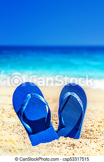 6c1ab3d71 Summer holiday beach background with flip flops on a tropical beach.  Slippers from a sand