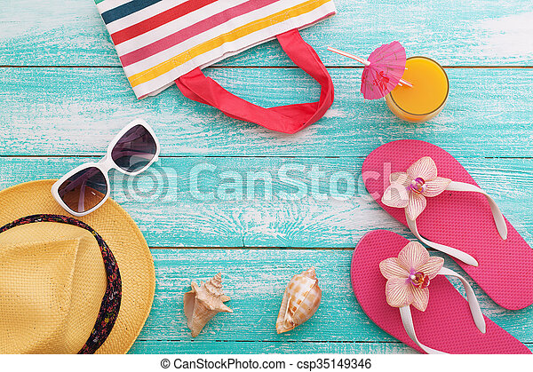 Summer Holidays in Beach Seashore. Summer drinks. Summer rest. Fashion accessories summer flip flops, hat, sunglasses on bright turquoise board near the pool