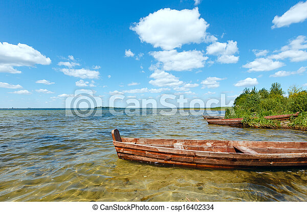 Summer lake view with wooden boats. - csp16402334
