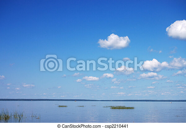 Summer landscape with quiet water of lake and cloudy sky - csp2210441