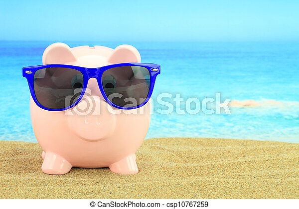 Summer piggy bank with sunglasses on the beach  - csp10767259